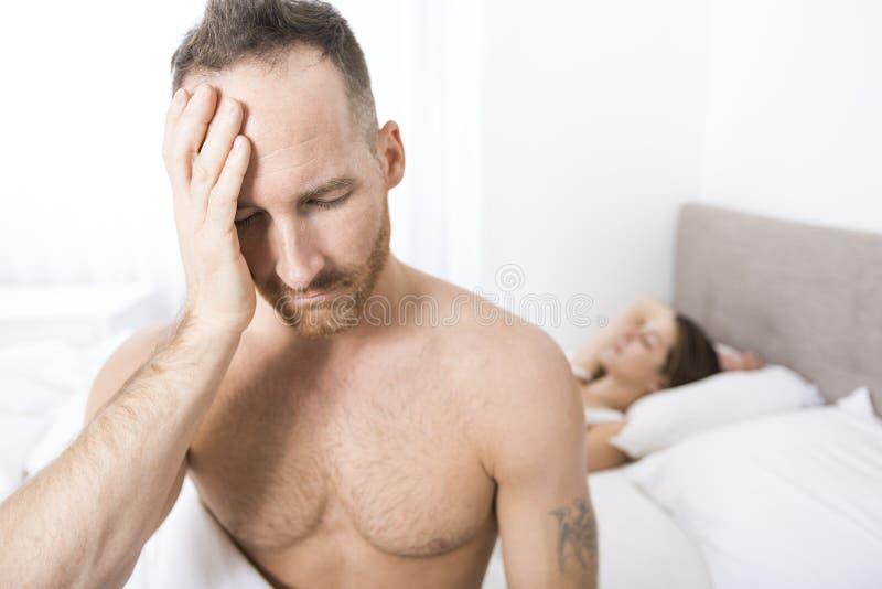 坐在床边缘的沮丧的人在卧室 免版税库存图片