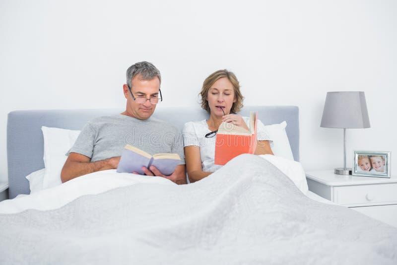 坐在床阅读书的愉快的夫妇 免版税图库摄影