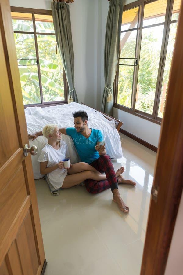 坐在床附近的年轻夫妇,早晨使用细胞巧妙的电话的愉快的微笑西班牙男人和妇女 图库摄影