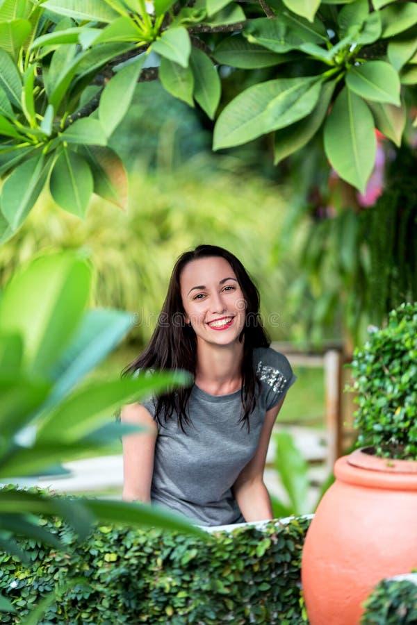 坐在庭院里的女孩,在绿色树中 库存照片
