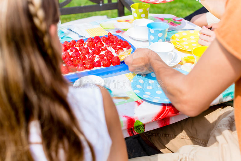 坐在庭院里的家庭有咖啡和蛋糕 库存照片