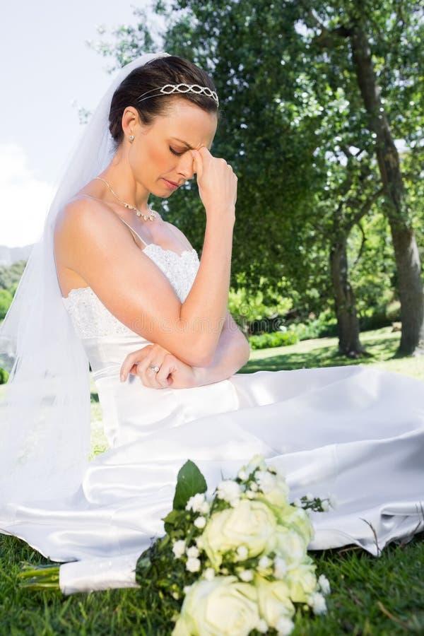 坐在庭院里的沮丧的新娘 库存照片