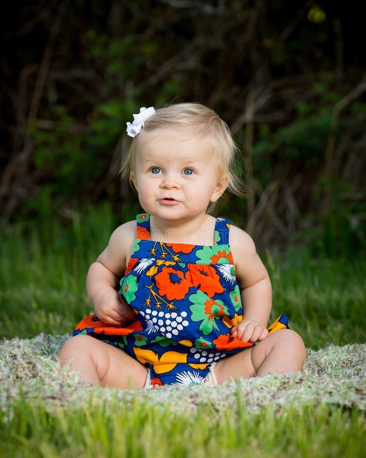 坐在开花的礼服的逗人喜爱的小孩 库存图片