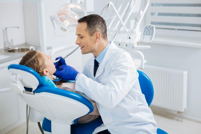 坐在患者附近的正面快乐的医生 免版税库存图片