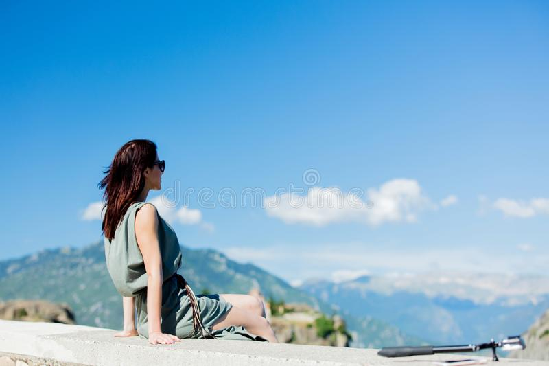 坐在悬崖的妇女在希腊 免版税库存照片