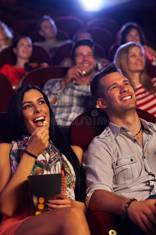 坐在戏院微笑的新夫妇 免版税库存图片