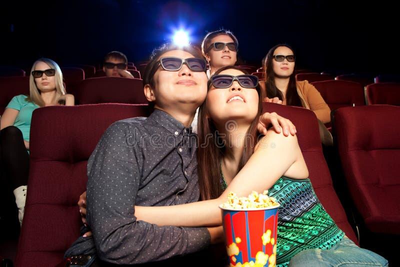 坐在戏院的年轻夫妇,观看影片 图库摄影