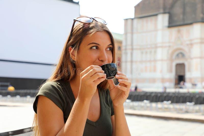 坐在户外咖啡馆在意大利,饮用的咖啡的微笑的美女画象 免版税图库摄影