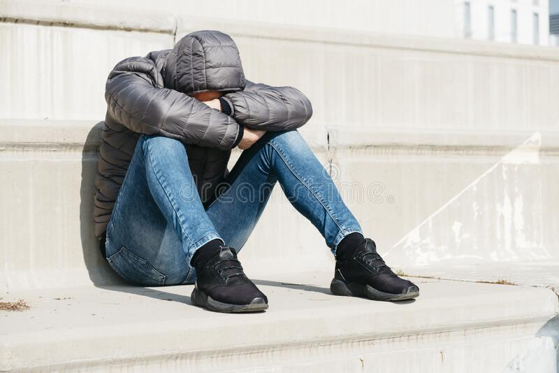 坐在户外楼梯上的男人蜷缩起来 免版税库存照片
