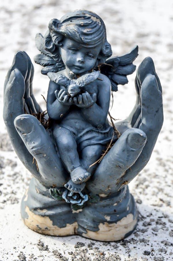 坐在手上的小天使拿着鸟 免版税图库摄影