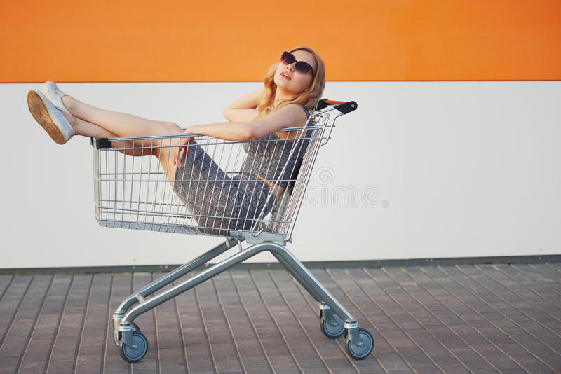 坐在手提篮的美丽的白肤金发的女孩 免版税库存图片