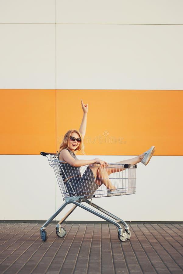坐在手提篮的美丽的白肤金发的女孩 免版税库存照片