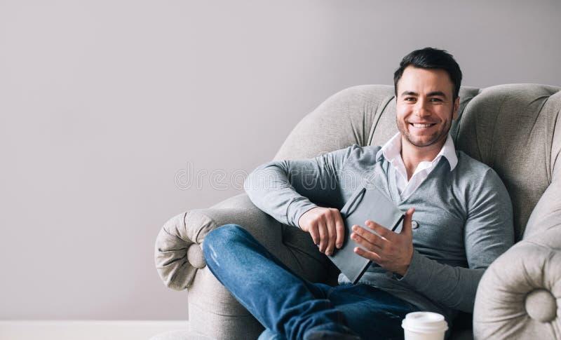 坐在扶手椅子和微笑的帅哥 免版税库存图片