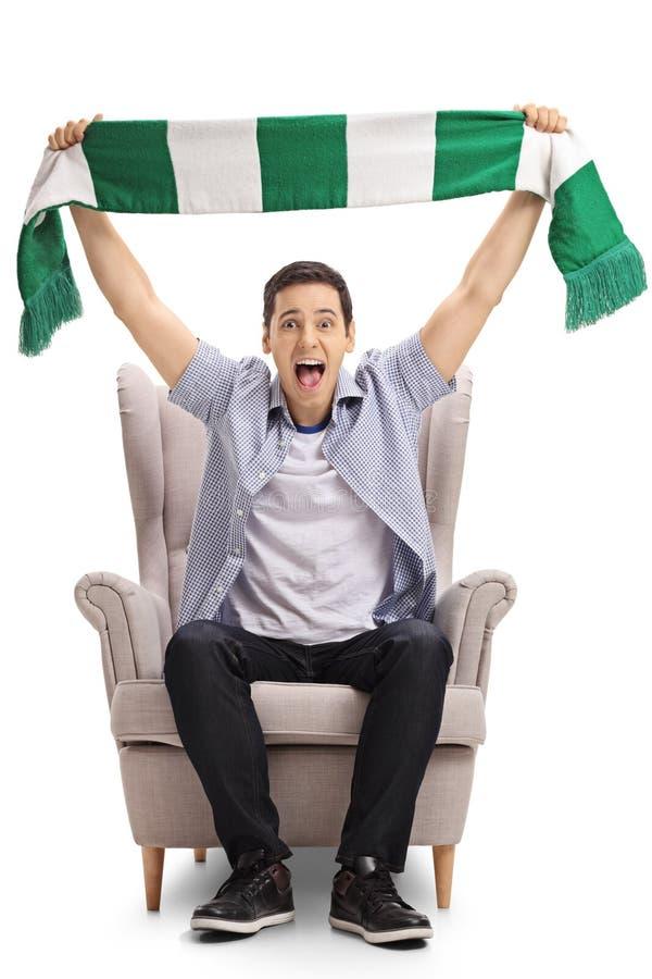 坐在扶手椅子和拿着围巾的激动的体育迷 免版税图库摄影