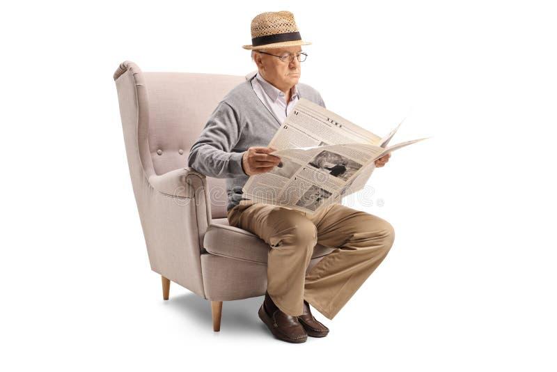 坐在扶手椅子和读报纸的老人 免版税库存图片