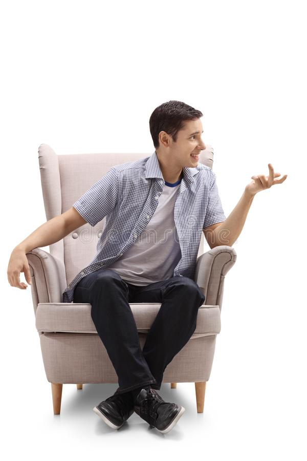 坐在扶手椅子和谈话的年轻人 免版税库存照片