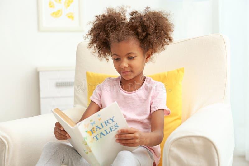 坐在扶手椅子和阅读书的一点非裔美国人的女孩在屋子里 库存图片