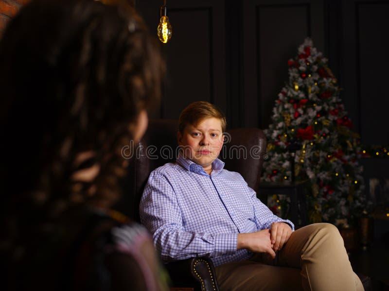 坐在扶手椅子的一个年轻人的画象在圣诞前夕 免版税库存照片