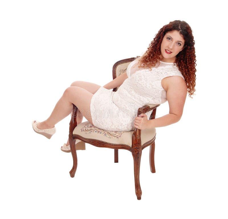 坐在扶手椅子的充分的计算的妇女 库存图片