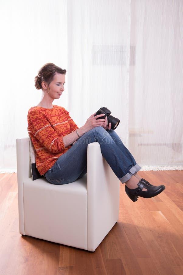 坐在扶手椅子的女性摄影师 库存图片