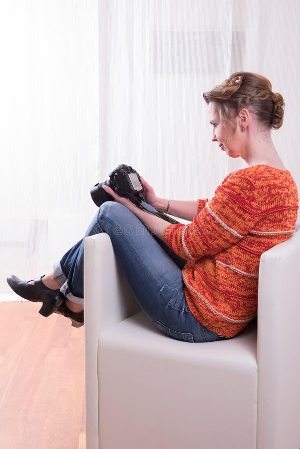 坐在扶手椅子的女性摄影师 库存照片