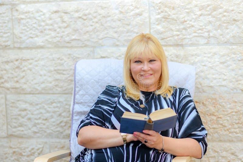 坐在扶手椅子的室外露台看书的美丽的中年微笑的斯堪的纳维亚妇女 免版税库存图片