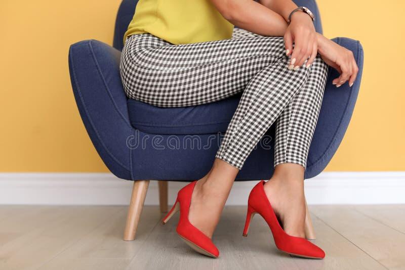 坐在扶手椅子的少妇穿红色鞋子 库存图片