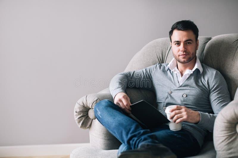 坐在扶手椅子的帅哥看  库存图片