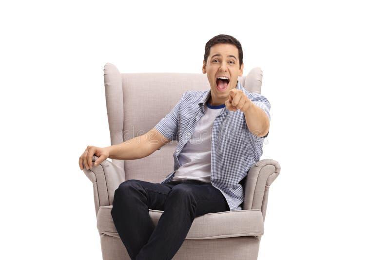 坐在扶手椅子的年轻人指向照相机和大声笑  库存图片