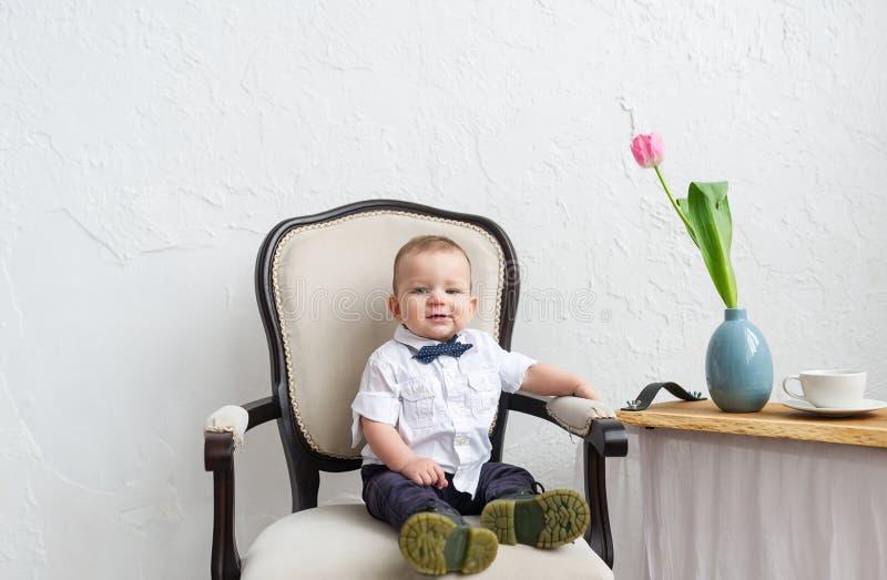 坐在扶手椅子的时兴的男婴在绝尘室 免版税库存照片