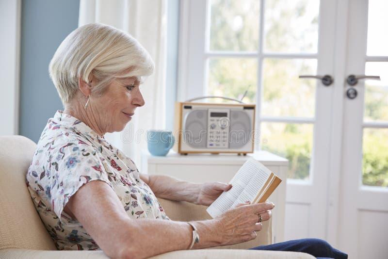 坐在扶手椅子的资深妇女在家读书 库存图片