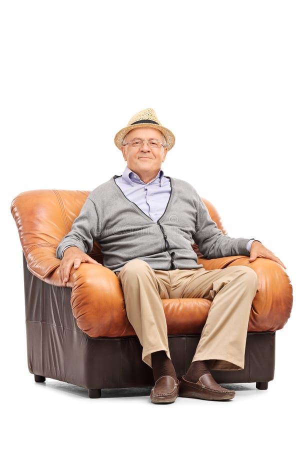 坐在扶手椅子的轻松的资深绅士 免版税库存图片