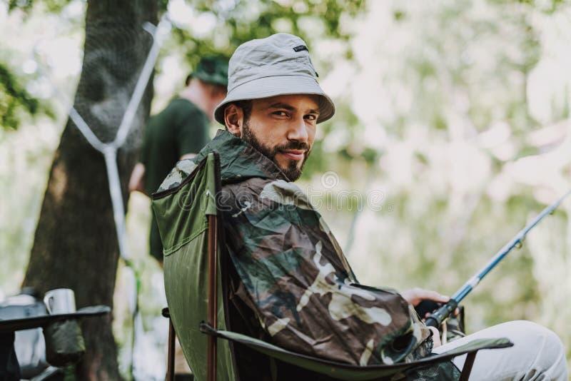 坐在折叠椅的宜人的有胡子的人 图库摄影