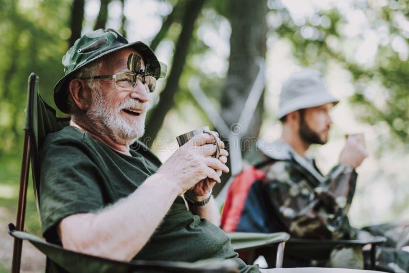 坐在折叠椅的正面微笑的年长人 免版税库存照片