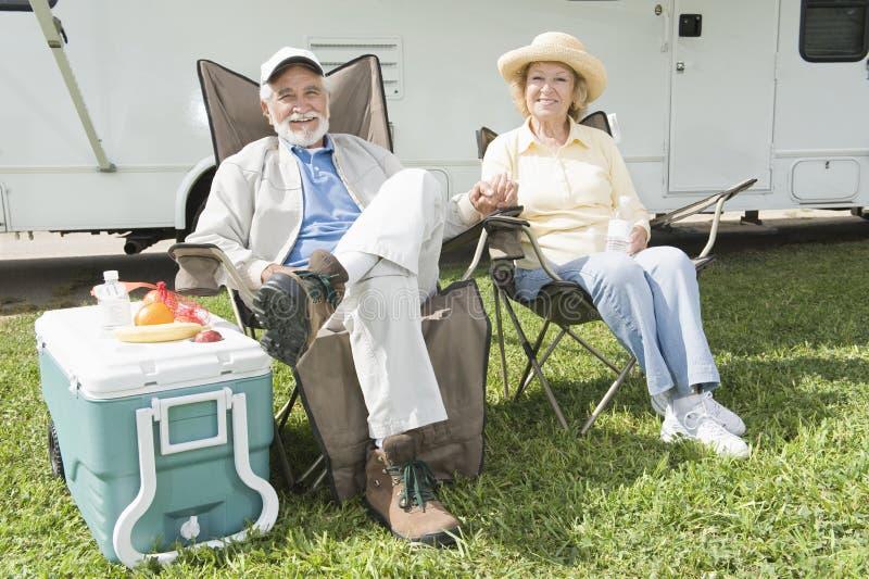 坐在折叠椅的轻松的夫妇 免版税库存图片