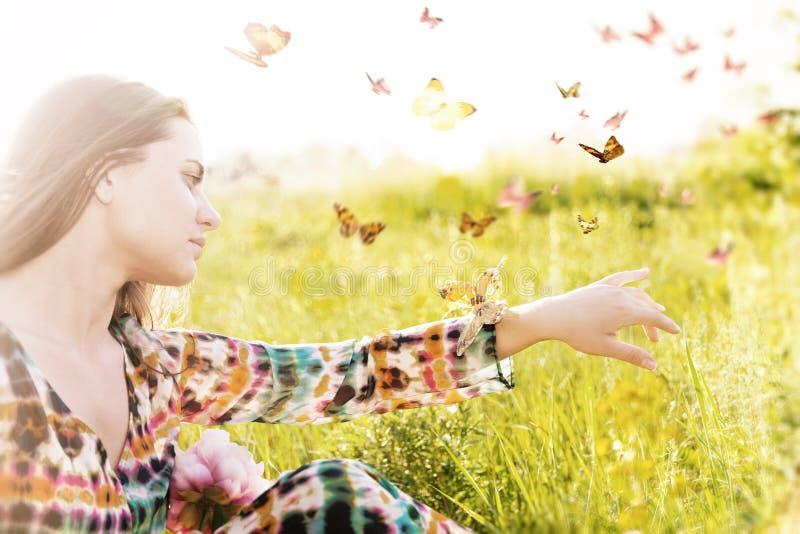 坐在掠过的蝴蝶群的一个草甸的女孩  免版税库存照片