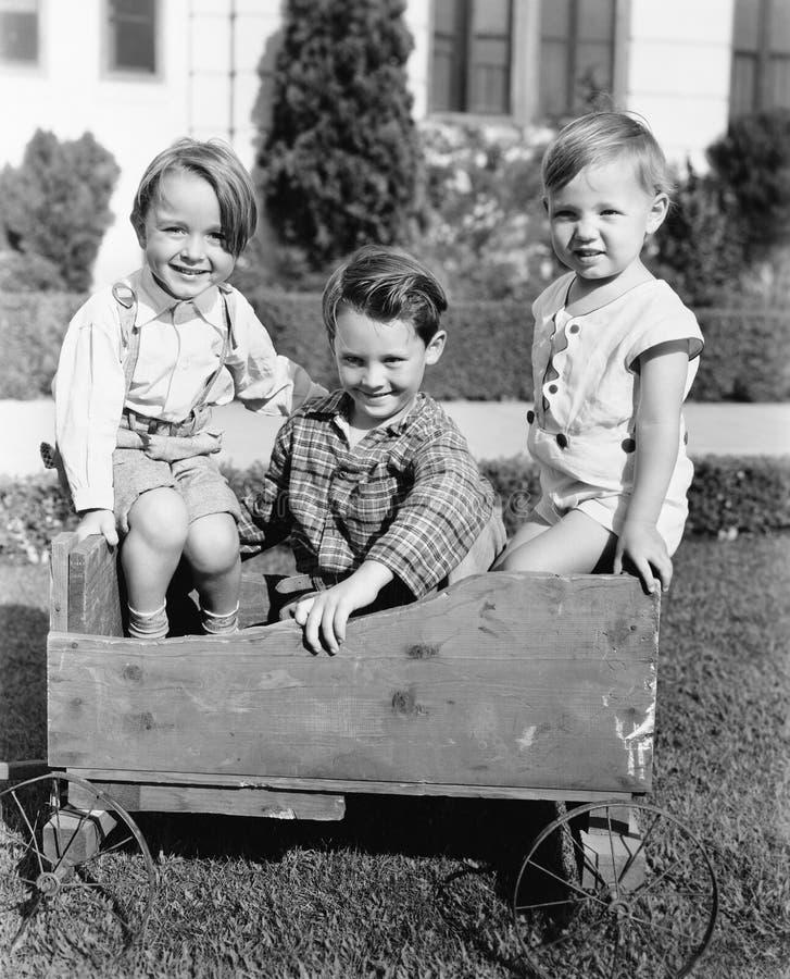 坐在推挤推车和微笑的三个男孩(所有人被描述不更长生存,并且庄园不存在 供应商warranti 免版税库存图片