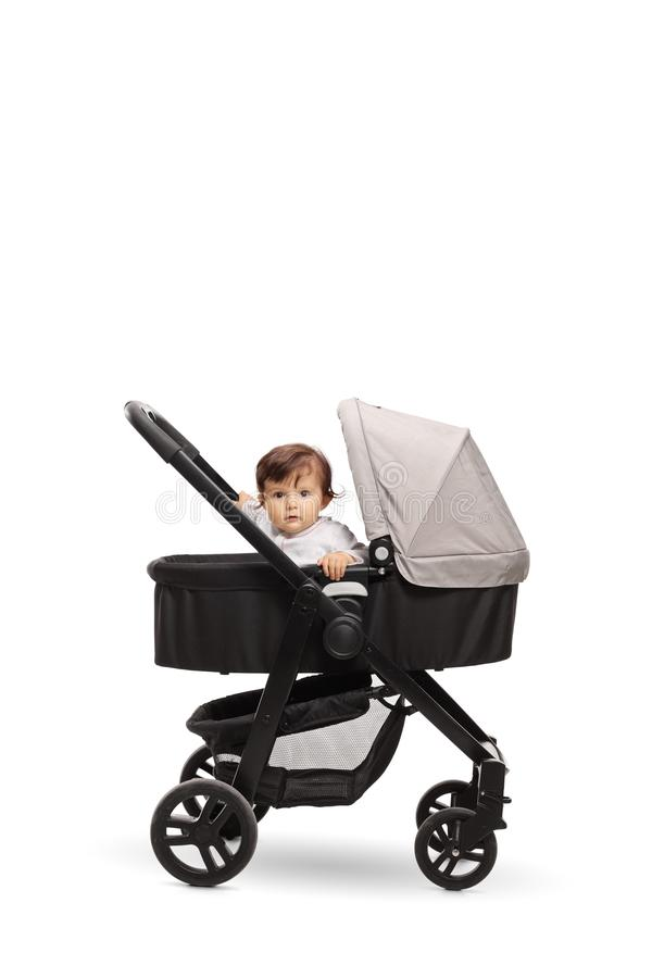 坐在摇篮车婴儿推车的可爱宝贝 免版税图库摄影