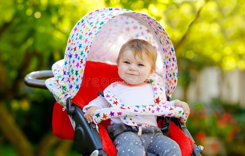 坐在摇篮车或婴儿推车和等待妈妈的逗人喜爱的健康矮小的美丽的女婴 愉快的微笑的孩子与 库存图片