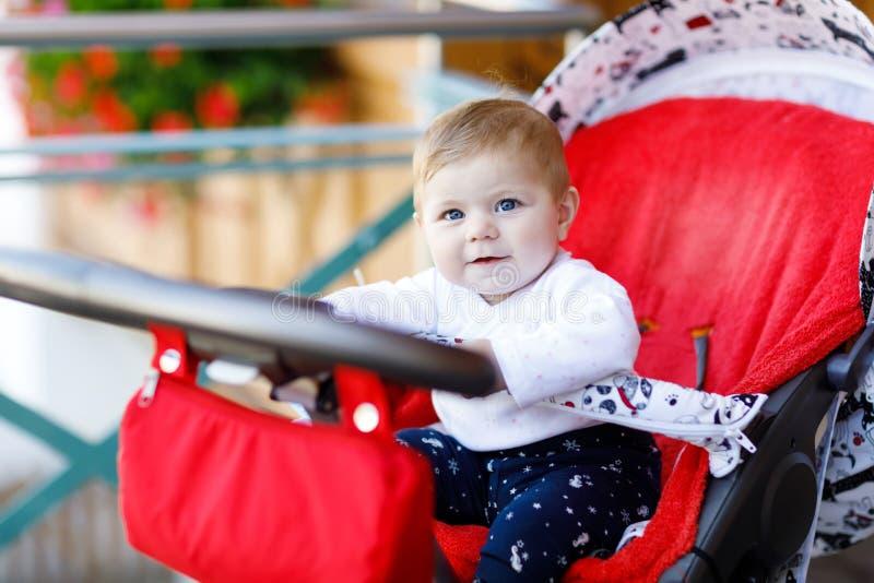 坐在摇篮车或婴儿推车和等待妈妈的6个月的逗人喜爱的矮小的美丽的女婴 库存图片