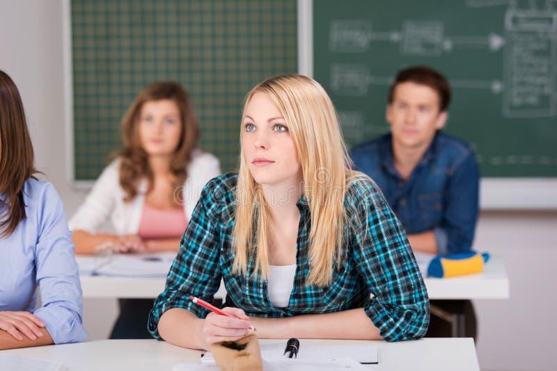 坐在教室的女性白肤金发的学生 免版税库存图片