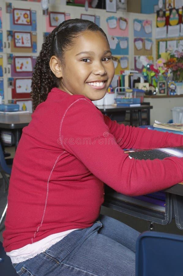 坐在教室的青春期前女孩 免版税图库摄影