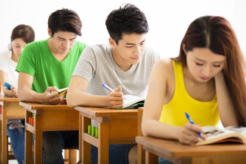 坐在教室的年轻大学生小组 免版税库存图片