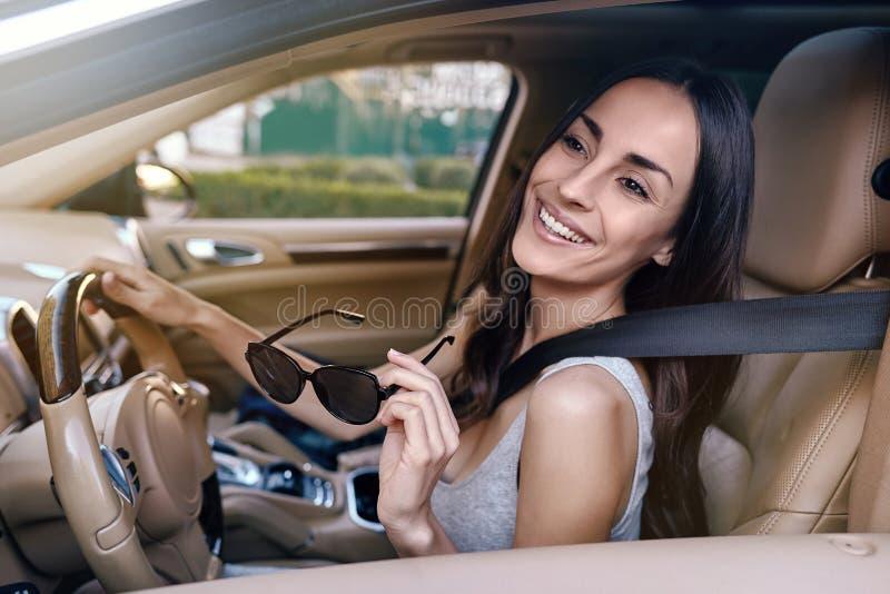 坐在新的汽车和把握关键的妇女 库存照片