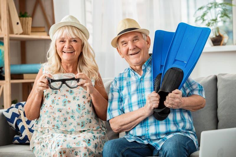 坐在旅行社里的一对老夫妇拿着游泳面具,嬉戏地笑着 库存图片