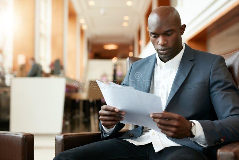 坐在旅馆大厅的商人使用手机和膝上型计算机 库存图片