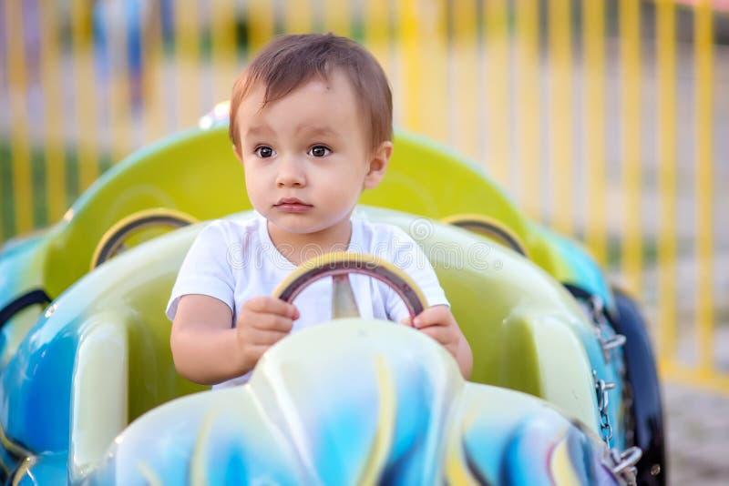 坐在旋转木马的一点汽车在主题乐园和拿着方向盘的小孩男孩画象 未来赛车手 库存照片