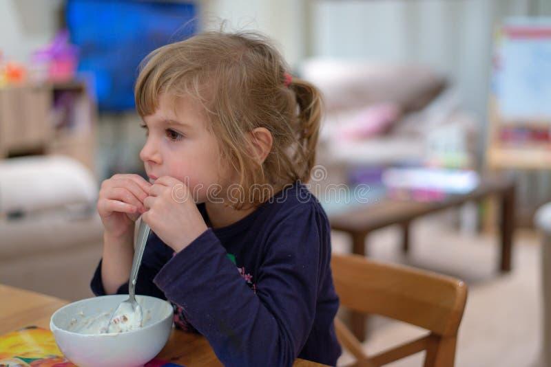 坐在早餐吃muesli的女孩用从白色碗的酸奶 免版税库存照片