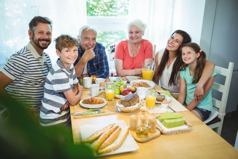 坐在早餐桌上的愉快的多代的家庭画象  免版税图库摄影