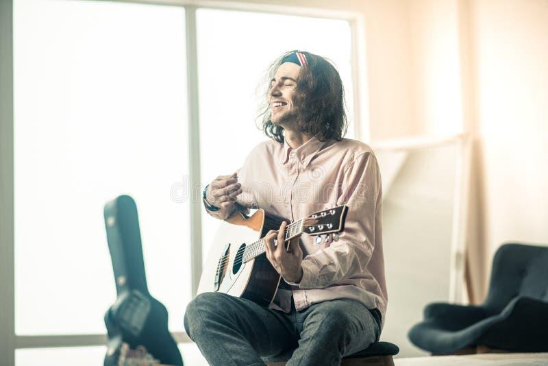 坐在明亮的屋子里的快乐的英俊的年轻吉他弹奏者 免版税库存图片